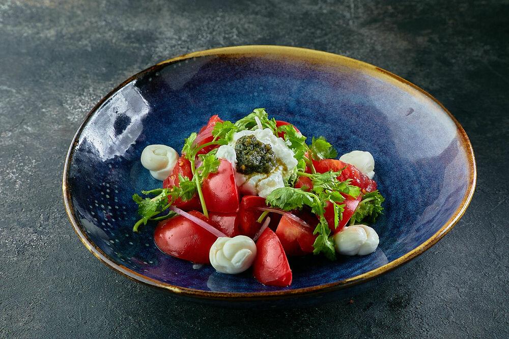 Pink tomato salad with yogurt and adjika sauce