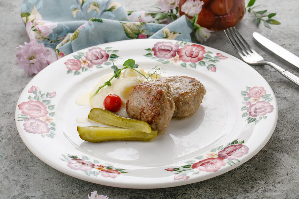 Veal and pork homemade cutlets with mashed potatoes  and pickled cucumber