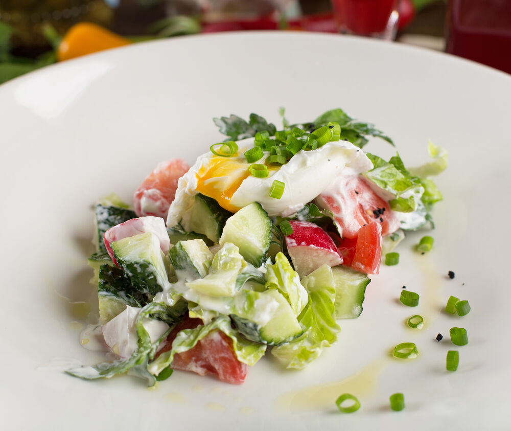 Homemade fresh vegetable salad with sour cream and poached egg