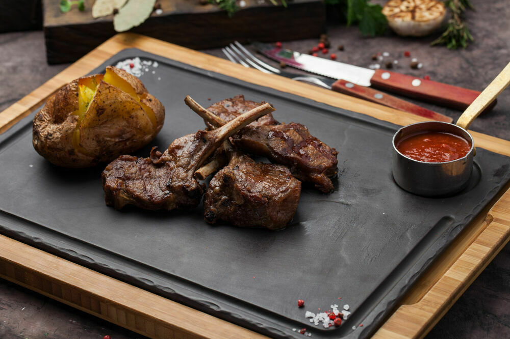 Charcoal grilled lamb ribs with baked potatoes