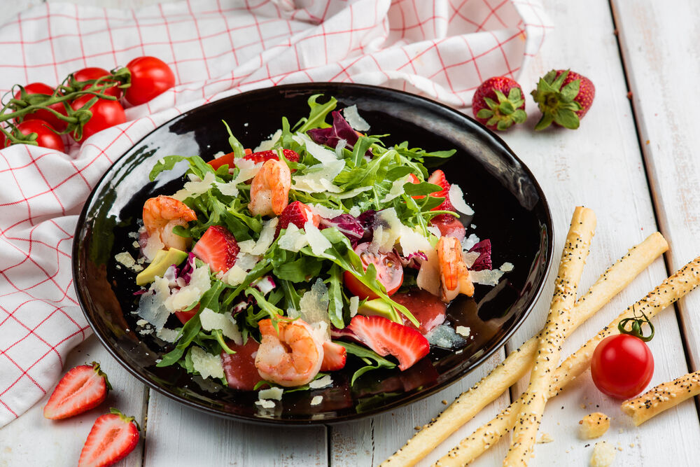 Leaves arugula with shrimp, cherry tomatoes and fresh strawberries