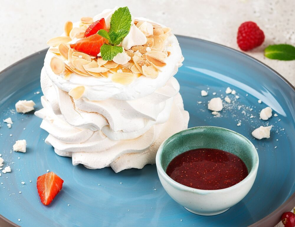 Meringue with creamy icing and berry sauce