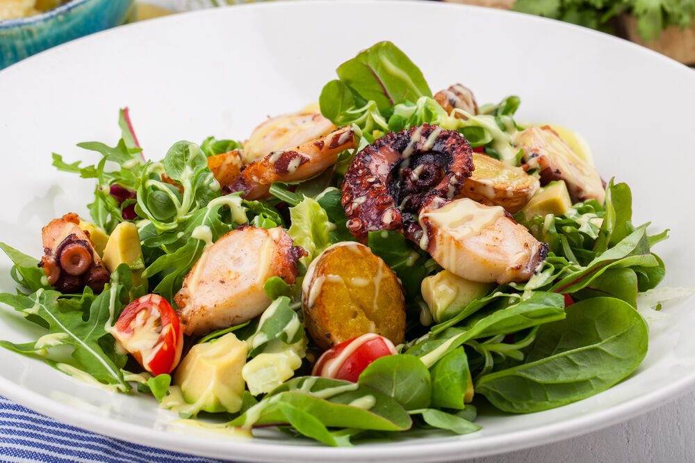 Salad with roasted octopus, avocado and tomatoes