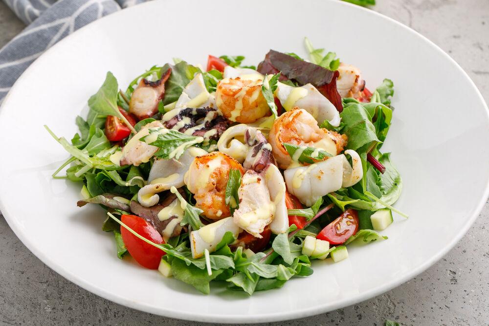 Salad with seafood and orange sauce
