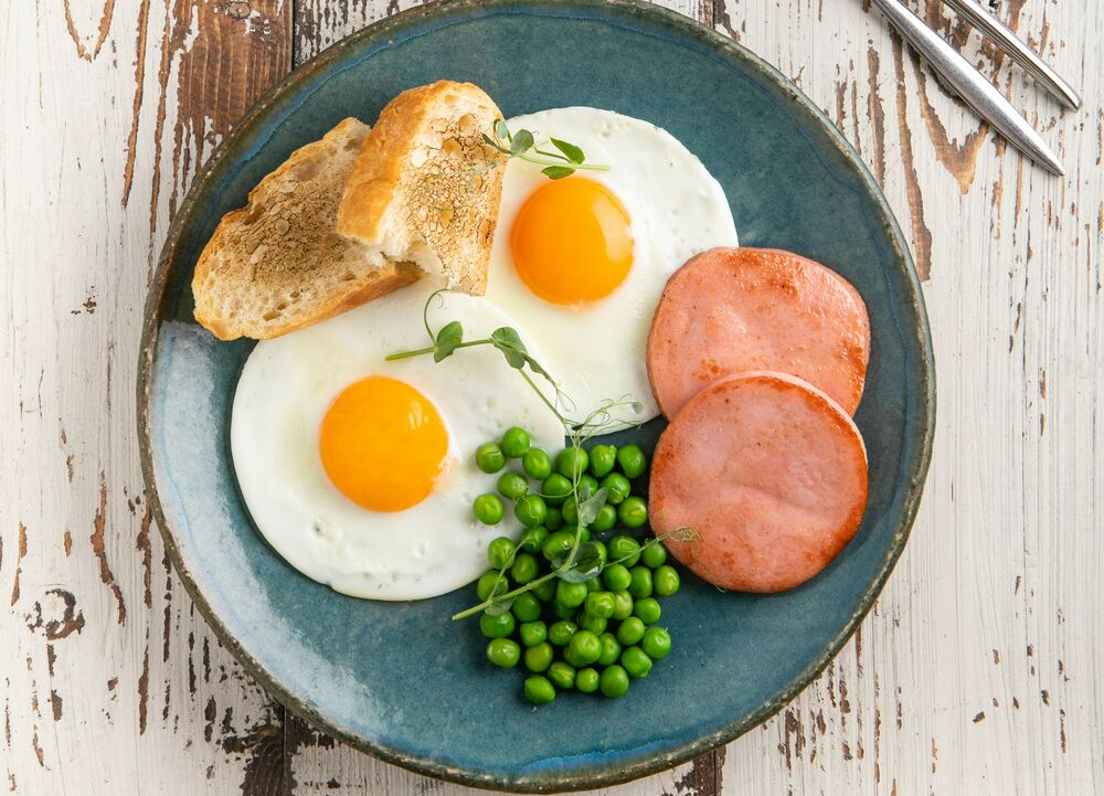 Fried eggs with ham and green peas