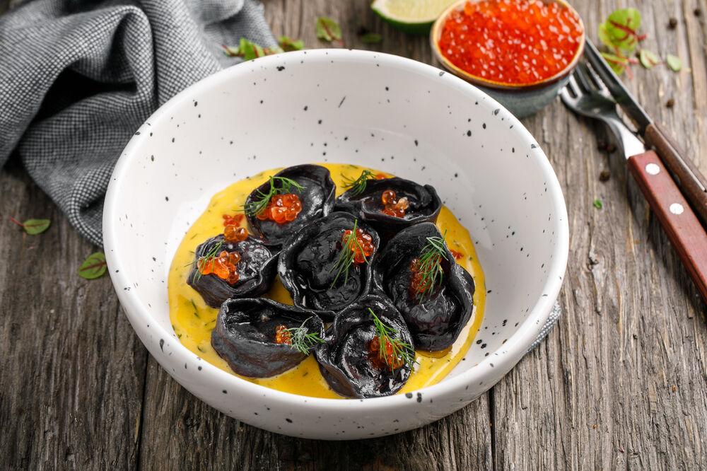 Homemade dumplings with salmon and red caviar