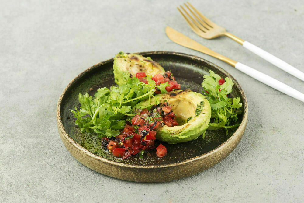 Baked avocado with tomato salsa and poached egg