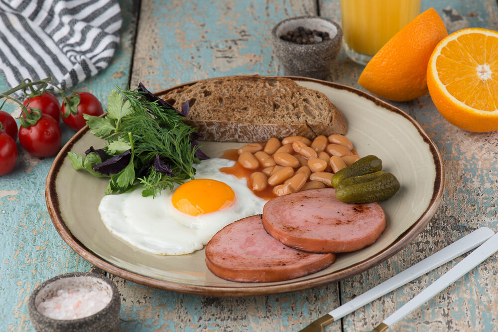 English style fried eggs with ham, beans and carnichons