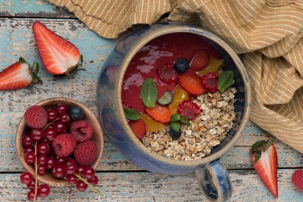 Granola with bright raspberry and strawberry smoothie