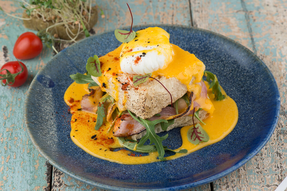Egg Benedict with fried bacon and champignons